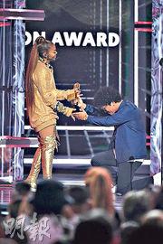 Bruno Mars(右)下跪頒獎予珍納積遜(左)。(法新社)