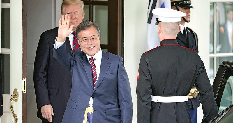 韓國總統文在寅(前左)昨到訪白宮,美國總統特朗普(後左)在場迎接。文在寅此行要務之一是向特朗普解釋朝鮮立場,力挽美朝峰會。(法新社)