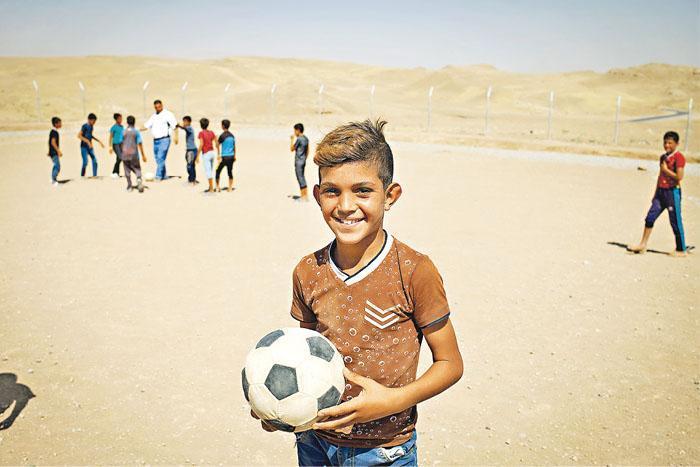 伊拉克的Hassan Sham營區聚居不少受戰亂影響的兒童,他們在足球場上重拾難得的笑顏。(圖:Abbie Trayler-Smith/樂施會提供)
