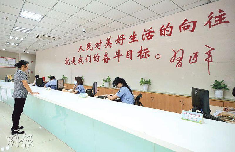 改革開放40年,中央再激勵幹部「敢作敢為」,杜絕懶政。圖為深圳社區服務中心,印有習語錄。(中新社)
