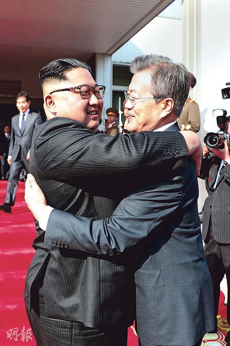 金正恩(左)和文在寅(右)會談前,於板門店擁抱,是1個月以來第2次文金會。(法新社)