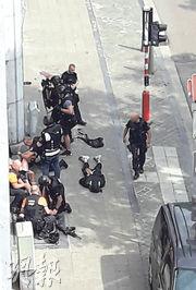 比利時列日市周一發生殺警案,多名警員趕到後站在相信是涉案疑犯(中)的旁邊。(路透社)
