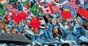 美國國務院表示,將限制部分中國留學生的簽證有效期。圖為5月16日,在美國哥倫比亞大學第264屆畢業典禮上,中國留學生在畢業禮上揮舞五星紅旗。(新華社)