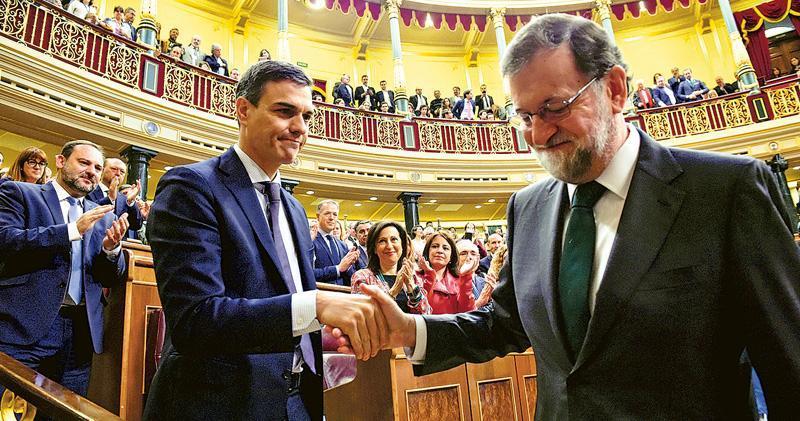 西班牙工人社會黨提出的不信任動議獲通過後,該黨總書記桑切斯(左)隨即接替被逼宮的拉霍伊(右)當上首相。圖為兩人昨日在國會內握手。(路透社)