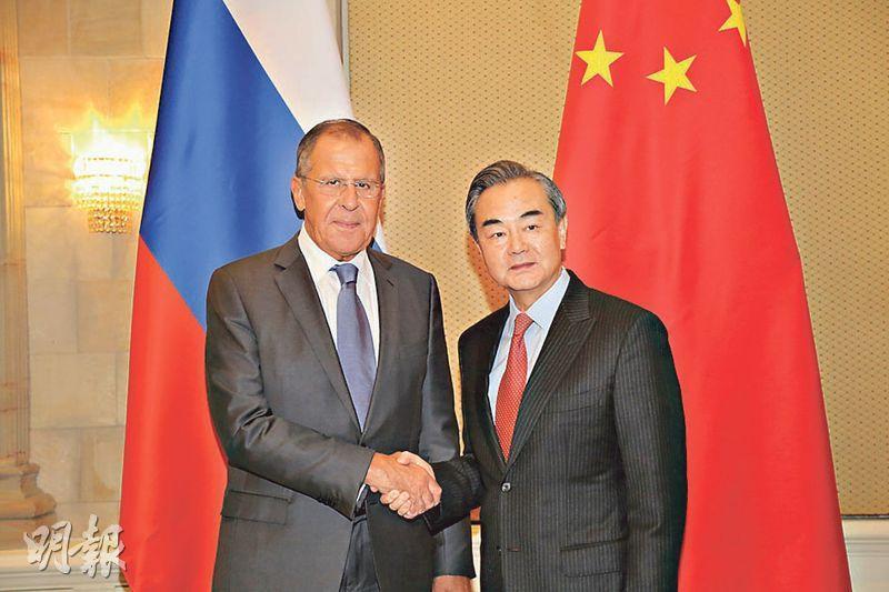 國務委員兼外長王毅(右)在南非會見俄外長拉夫羅夫(左),稱中俄應進一步加強協調合作,維護新興市場和發展中國家整體利益。(中新社)