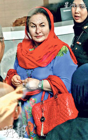 馬來西亞前首相納吉布的妻子周二帶着名牌Versace的紅色手袋,接受反貪委員會問話調查。(網上圖片)