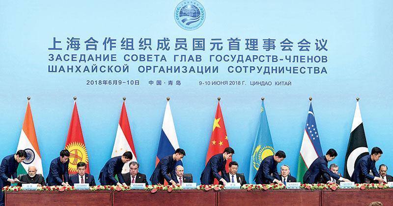 上合組織青島峰會,成員國昨日簽署《青島宣言》。圖為中國國家主席習近平(席上左五)與俄羅斯、印度等其他7個成員國元首簽署峰會共識的《青島宣言》。(路透社)