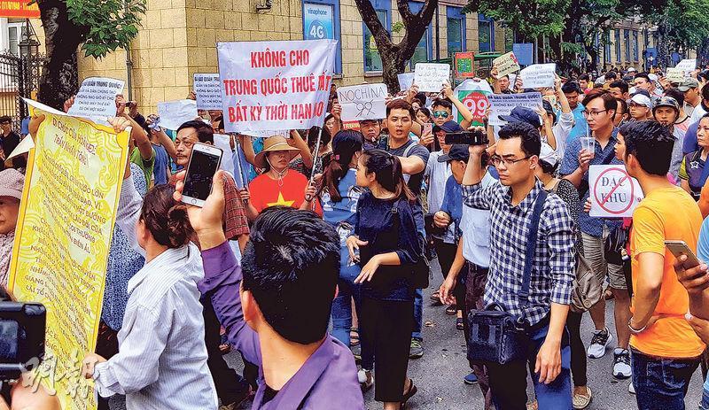 在越南河內,周日有示威者舉起寫有「任何時候也不租地予中國」標語的橫額,抗議政府計劃通過經濟特區法草案,延長外商租地年限至99年。(路透社)