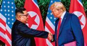 朝鮮領導人金正恩(左)與美國總統特朗普(右)昨在新加坡舉行歷史峰會,兩人在簽署聯合聲明後握手,特朗普拉着金正恩的手疑似想把他拉近自己,但看來並不成功。(法新社)