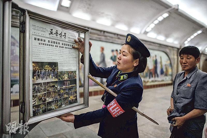朝鮮地鐵站職員昨天更換車站月台報紙欄內的《勞動新聞》。該官媒昨天頭版圖文並茂報道金正恩夜遊新加坡的消息。(法新社)