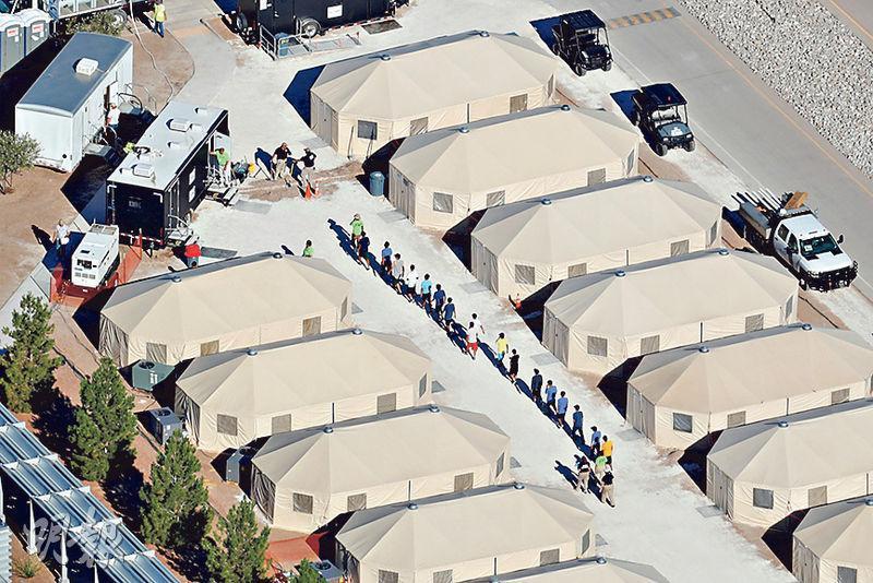 無監護人陪伴的非法入境兒童周一在靠近墨西哥的得州托尼洛搭建的「帳篷城」排成一行(中央),等候美國當局分配安置。(路透社)