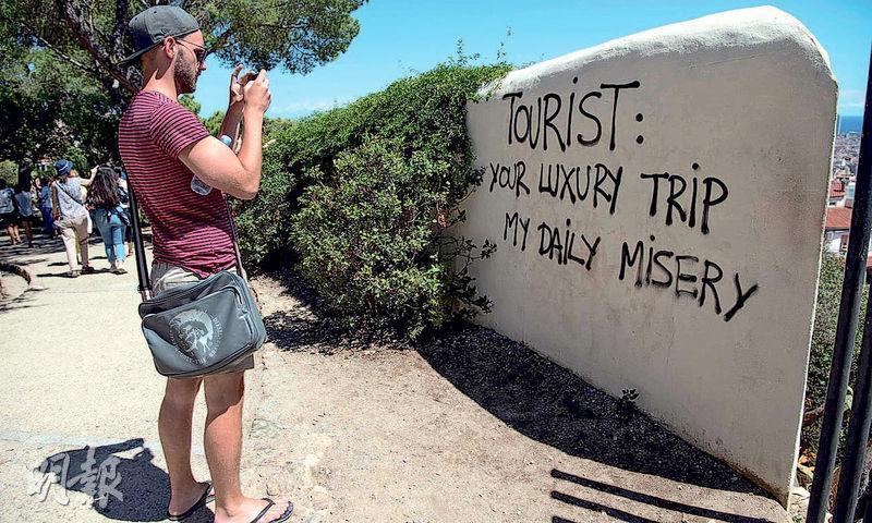 巴塞隆拿一個公園有人塗鴉留言,寫着「遊客﹕你的豪華旅程,我的日常苦難」,表達反遊客立場。(法新社)