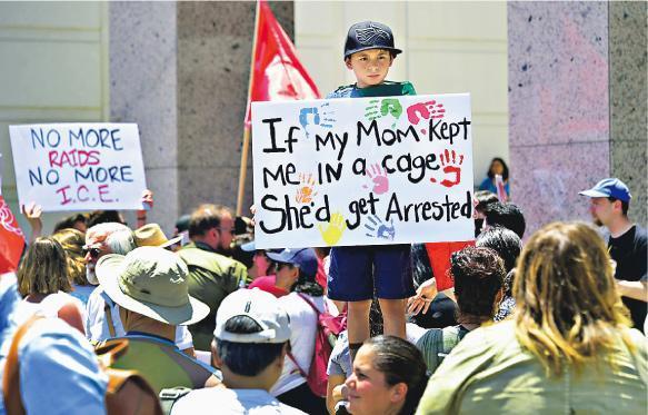 在洛杉磯上周六有小童參與示威,抗議特朗普的零容忍政策。一名小孩舉起的標語寫着:「如果媽媽把我困在籠裏,她會被拘捕」,回應早前有關人蛇童被安置在鐵籠的報道。(法新社)