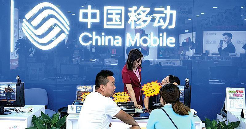 美國商務部官員透露,特朗普政府已建議駁回中國移動提出進入美國市場的申請。圖為重慶中移動營業廳內,職員為顧客服務。(中新社)