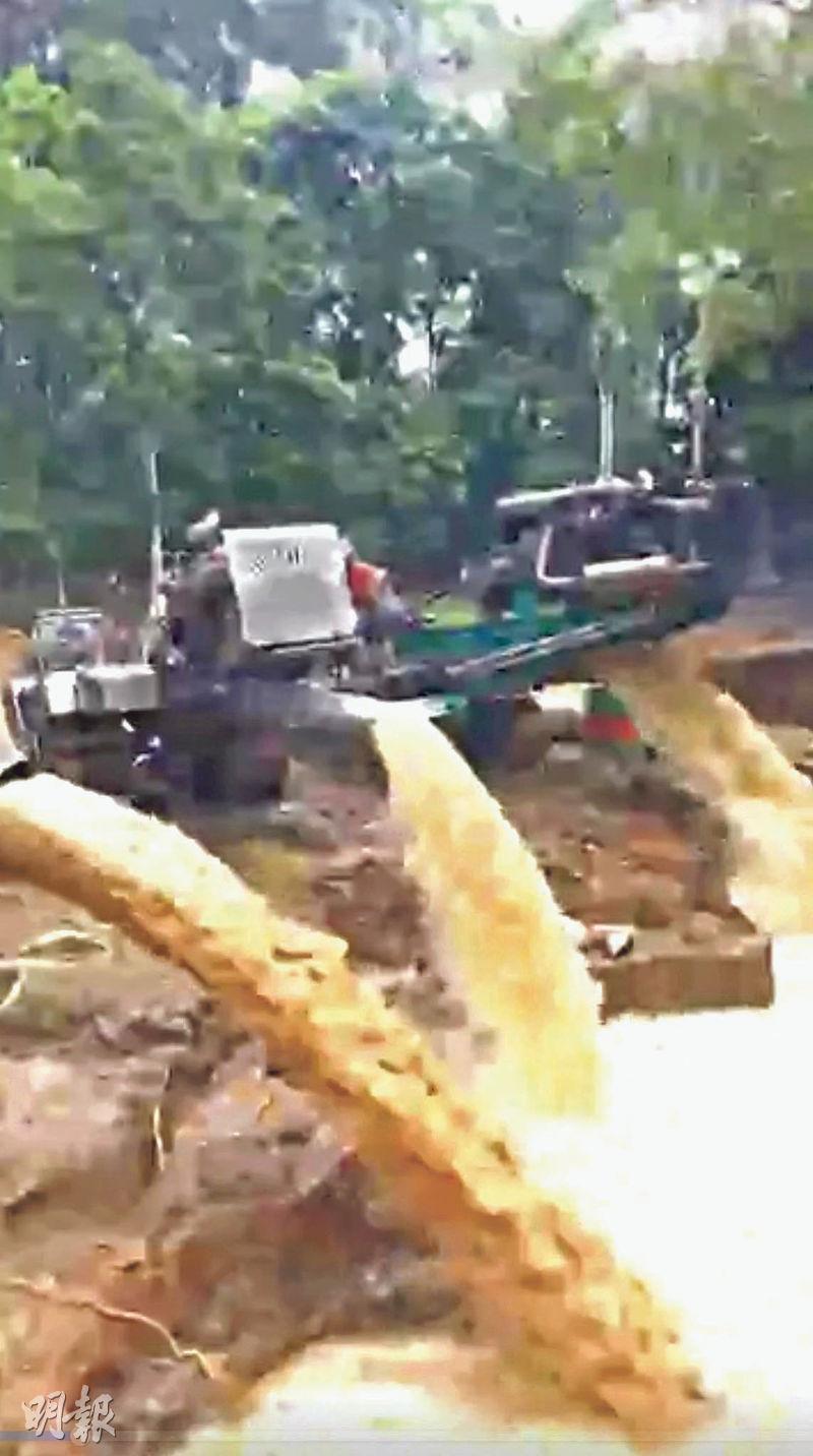 重型機械車輛在肇事洞穴附近不斷排出大量濁水。(路透社)