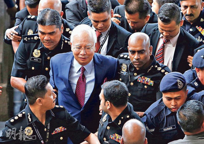 馬來西亞前首相納吉布(中)昨出庭應訊,他否認全部4項控罪,獲准保釋候審。(路透社)