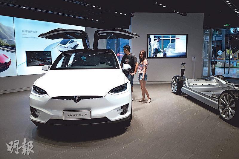 從今日起,產自美國的進口車關稅將上調至40%,Tesla等美國汽車將大受影響。圖為7月4日,人們參觀Tesla在北京的陳列室。(法新社)