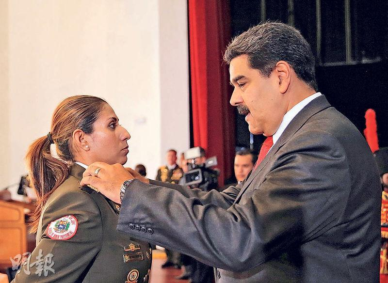 委內瑞拉總統馬杜羅(右)周一在加拉加斯為一名獲晉升的軍人更換肩章。(路透社)