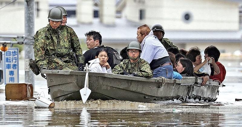 自衛隊昨日出動救出岡山縣倉敷市受洪水圍困的災民。(路透社)