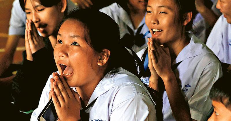 被困少年的同學昨日由老師口中得知部分人已獲救,有女同學表現雀躍和合十祈禱。(路透社)