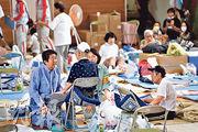 日本首相安倍晉三(左)昨到岡山縣探望災民。(法新社)