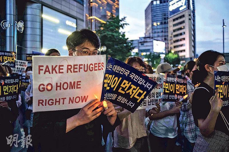 有韓國民眾出席上月30日在首爾的示威,舉標語牌要求假難民立即返回家鄉。(法新社)