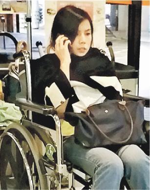 注射童顏針後不適的女子,送院時清醒,坐在輪椅等候分流。她不時作嘔,醫護人員在其胸前掛上白色膠袋,以備不時之需。(林智傑攝)