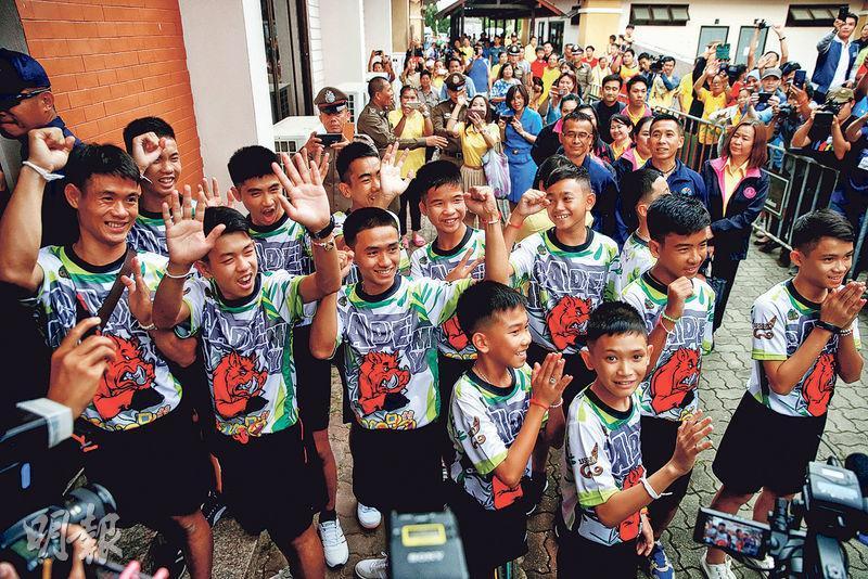 泰國「野豬」少年足球隊的副教練和12名隊員昨日抵達記者會現場,是他們脫困後首次公開亮相。(路透社)