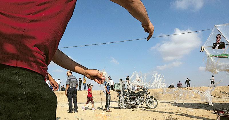 加沙巴人自4月在邊界發起回歸大遊行,有組織一直飄放綁有爆炸品的氣球及風箏飄去以色列領土內。(法新社)