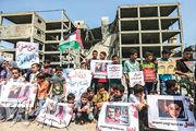 周日在加沙,有巴人青少年手持巴勒斯坦旗幟和海報標語在被炸毁建築前,抗議以軍空襲。(法新社)