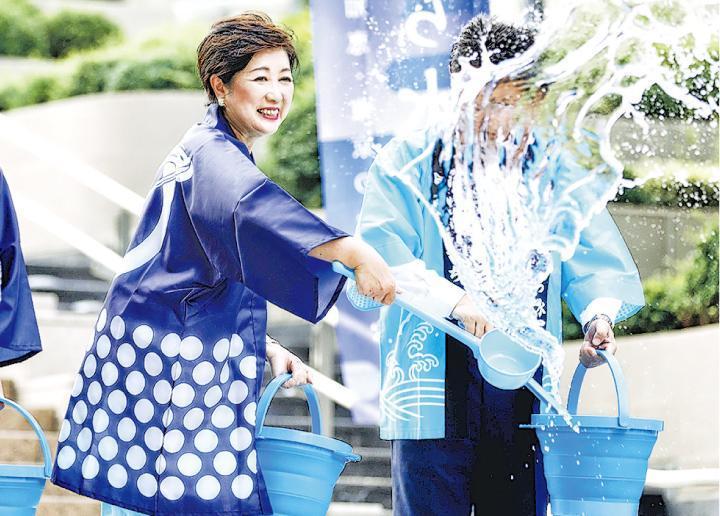 東京都知事小池百合子(左)昨在東京參與潑水降溫活動。日本熱浪持續,令人憂慮2020年7月舉行奧運時,運動員和觀眾可能中暑。(法新社)