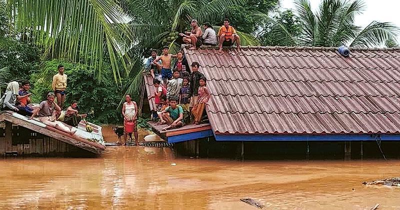 老撾一個水電站大壩坍塌,引發洪水淹沒多條附近村莊,有倖存村民躲到屋頂等待救援。(網上圖片)