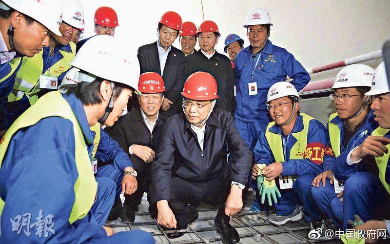 在西藏考察的總理李克強(中)前日在海拔3500米的川藏鐵路嘎拉山隧道,蹲下檢查施工質量,並與工人談話。(網上圖片)