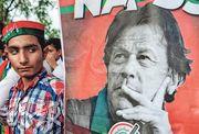 正義運動黨周四在黨魁伊姆蘭‧汗的伊斯蘭堡寓所附近舉行祝捷集會,一名巴基斯坦青年凝望着勢將出任總理的伊姆蘭‧汗的海報。(法新社)