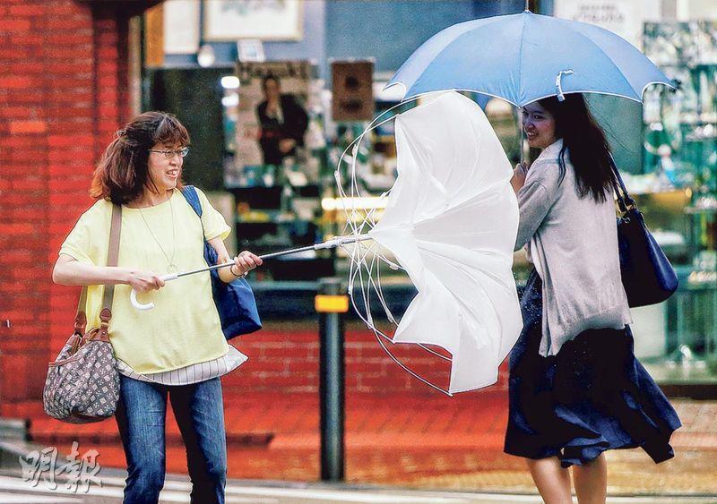 颱風「雲雀」逼近下,東京昨強風大雨,不少途人的雨傘打翻。(路透社)