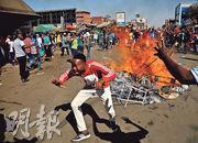 津巴布韋反對黨民主變革運動(民革運)的支持者,昨在首都哈拉雷街頭設障礙物和點火,抗議選舉不公。(路透社)