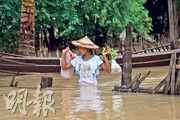 緬甸勃固區嚴重水浸,昨日水深及腰,有女子涉水而行。(法新社)