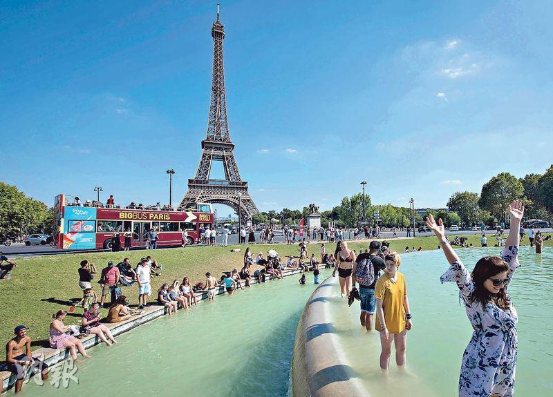 歐洲遇上逾40年來持續最久的熱浪,上周五不少巴黎市民踩進噴水池消暑。(法新社)