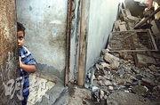 一名巴勒斯坦男童的家因以軍空襲而受損,他於空襲後站在家門口往外觀望。(路透社)