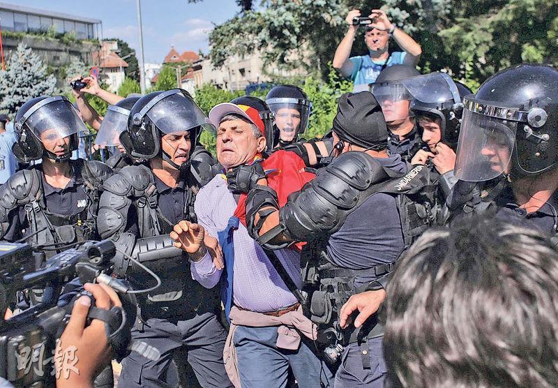 羅馬尼亞布加勒斯特的反政府集會上,有防暴警察抓住示威者頸項。(路透社)