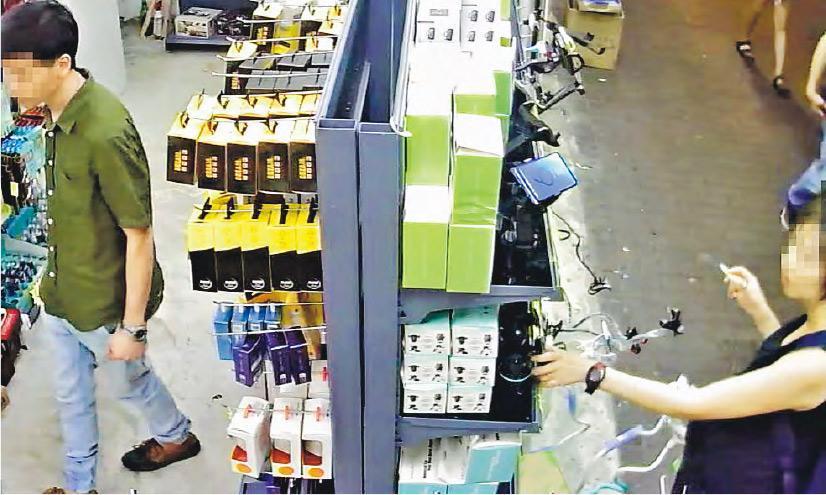 旺角有手機配件店失竊,店主發放閉路片段,可見穿綠色衫的男子在店內準備落手偷竊,身穿黑色連身裙的孕婦則在店外一邊抽煙一邊把風。(網片截圖)