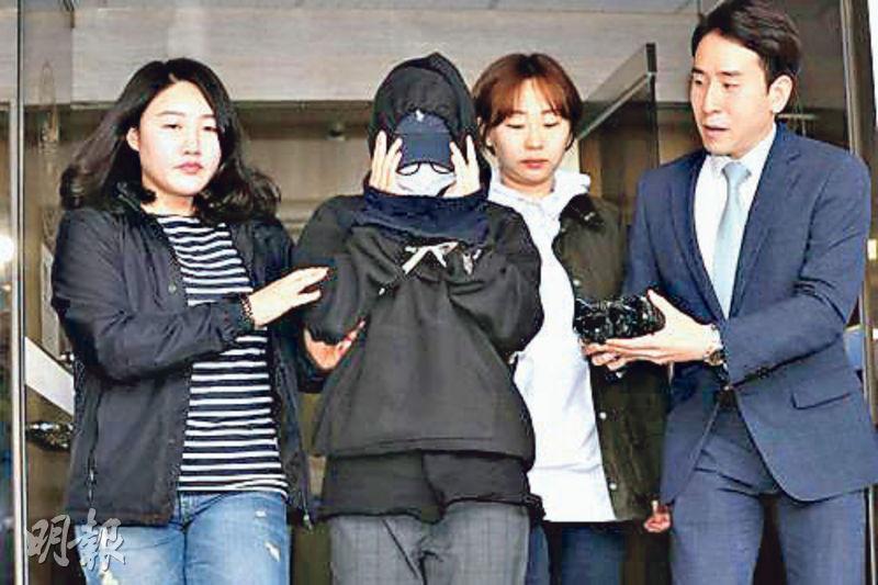 姓安的女模特兒(蒙面者)因偷拍及散播男同事裸照,昨被判囚10個月。圖為她5月12日到警署接受調查。(網上圖片)