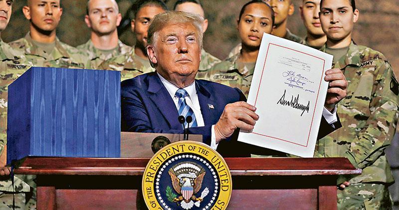 美國總統特朗普(前)前日在紐約州德拉姆堡基地(Fort Drum)簽署《2019財政年度國防授權法案》,其後展示簽名。該法案涉及中國及台灣部分惹來中國外交部、國防部等部門強烈不滿。(路透社)