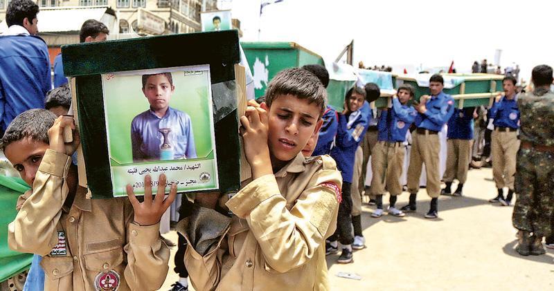 也門西北部薩達省達哈延市的群眾,8月13日為沙特聯軍空投美製炸彈殺害的校巴男童集體舉殯。(新華社)