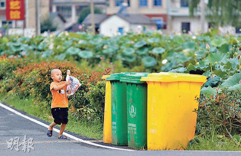 農村垃圾是「美麗鄉村」的治理難點,圖為浙江省安吉縣港口村,一名兒童準備將垃圾扔進村口的分類垃圾桶。(新華社)