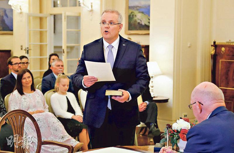澳洲新總理莫里森(前)昨日當選執政黨黨魁後,隨即宣誓就任總理。(路透社)