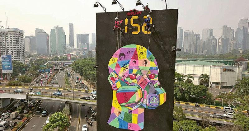 國際環保組織綠色和平趁亞運在印尼雅加達舉行,早前在當地豎立巨型廣告牌,強調有毒的污染空氣危害市民和亞運選手的健康。最新研究稱,空氣污染可損人類認知能力。(法新社)