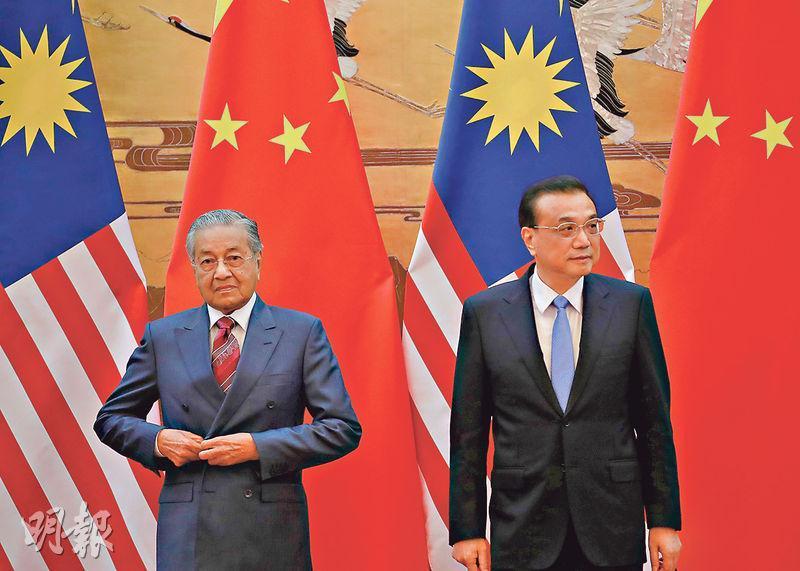 馬來西亞首相馬哈蒂爾(左)於本月中訪華期間,與總理李克強(右)會面,前者訪華時提出取消3個一帶一路項目。圖為兩人於上周一準備簽署備忘錄。(法新社)