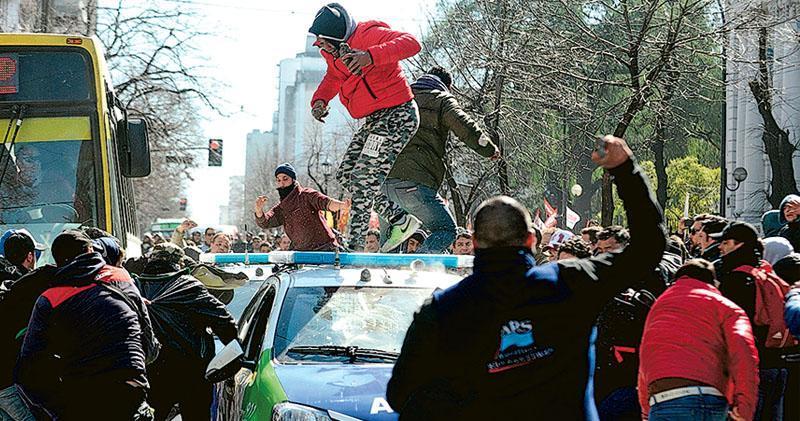 阿根廷經濟衰退,政府推出緊縮措施惹當地人不滿,觸發社會動盪。上周二於首都布宜諾斯艾利斯以南的拉普拉塔,有造船廠工人組織反緊縮示威,與警方起衝突。(法新社)