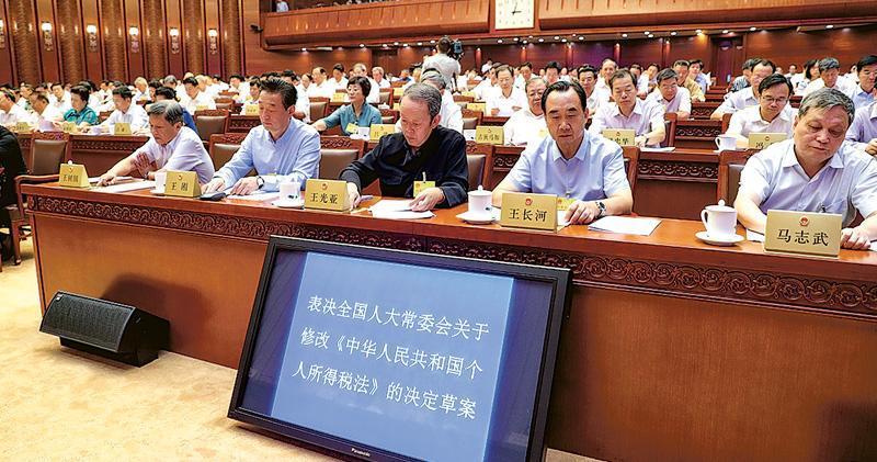 十三屆全國人大常委會第五次會議昨日在北京閉幕,會議表決通過個人所得稅法修正案。圖為全國人大常委王光亞(右二)等人在投票。(中新社)